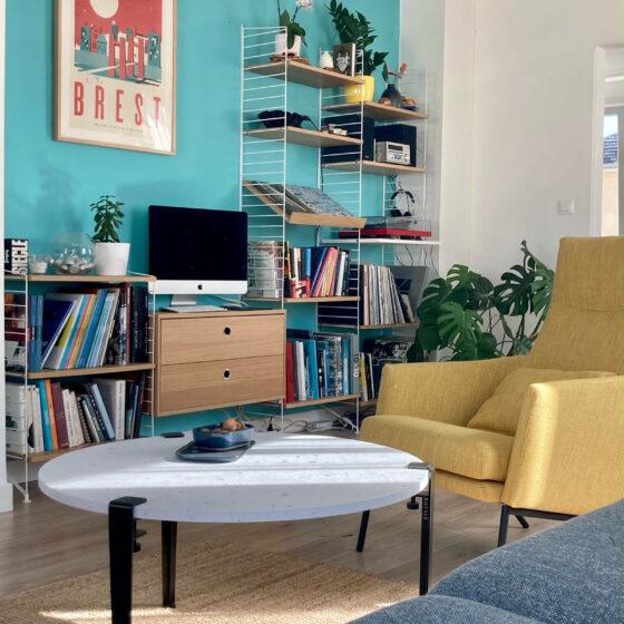 Composition mixte bibliothèque/hifi String, avec en premier plan la table basse Venezia de Tiptoe et le fauteuil Siri de Sits